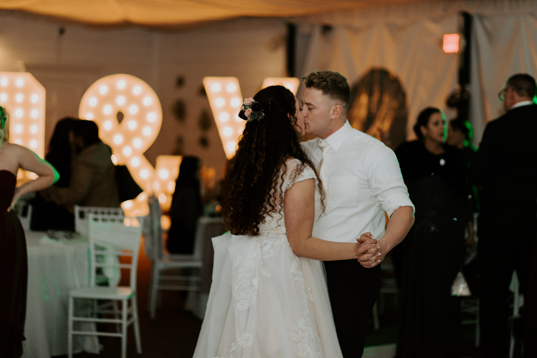 Bride and groom dancing in front of large light up letters