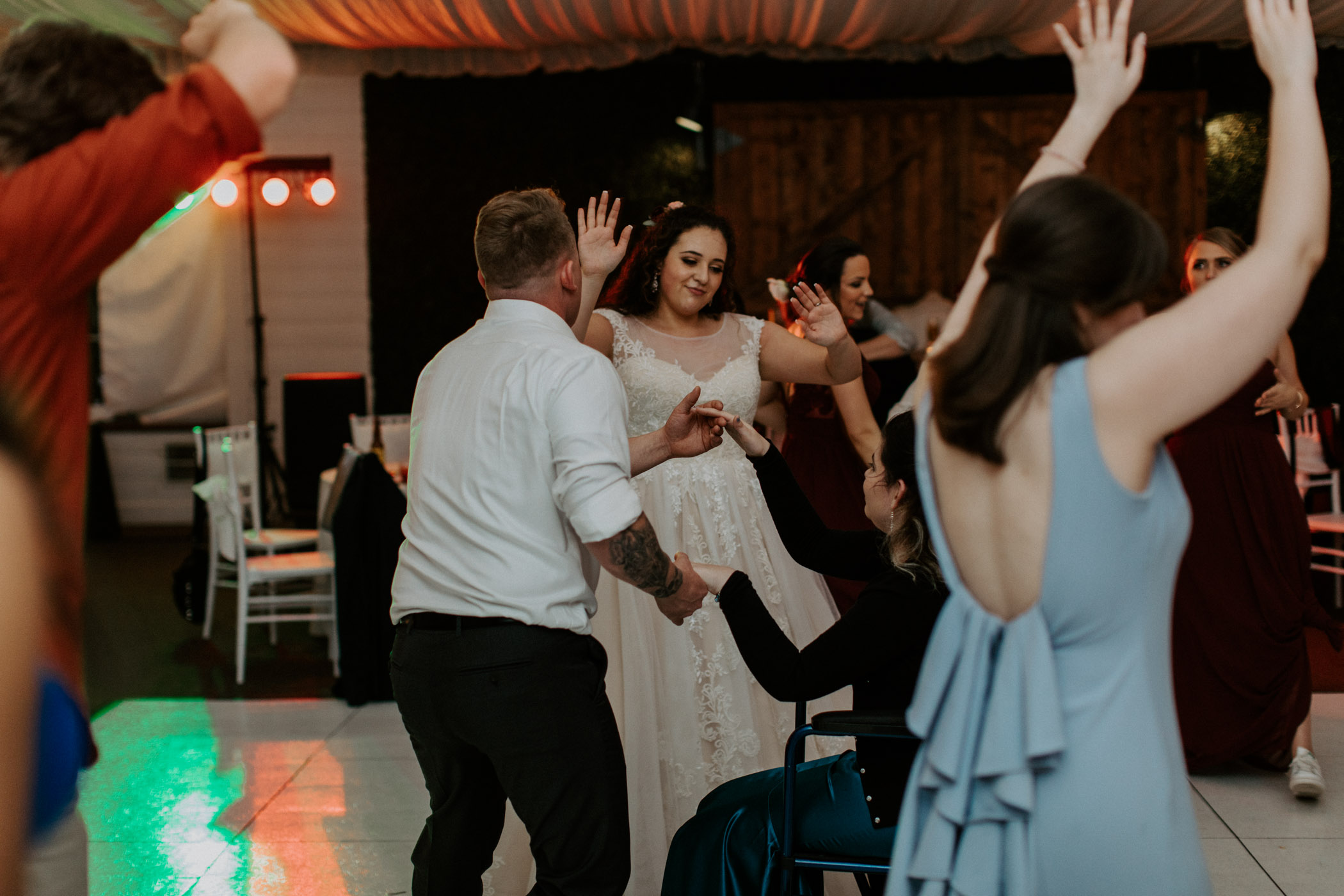 Bride dancing with her hands in the air a their wedding reception