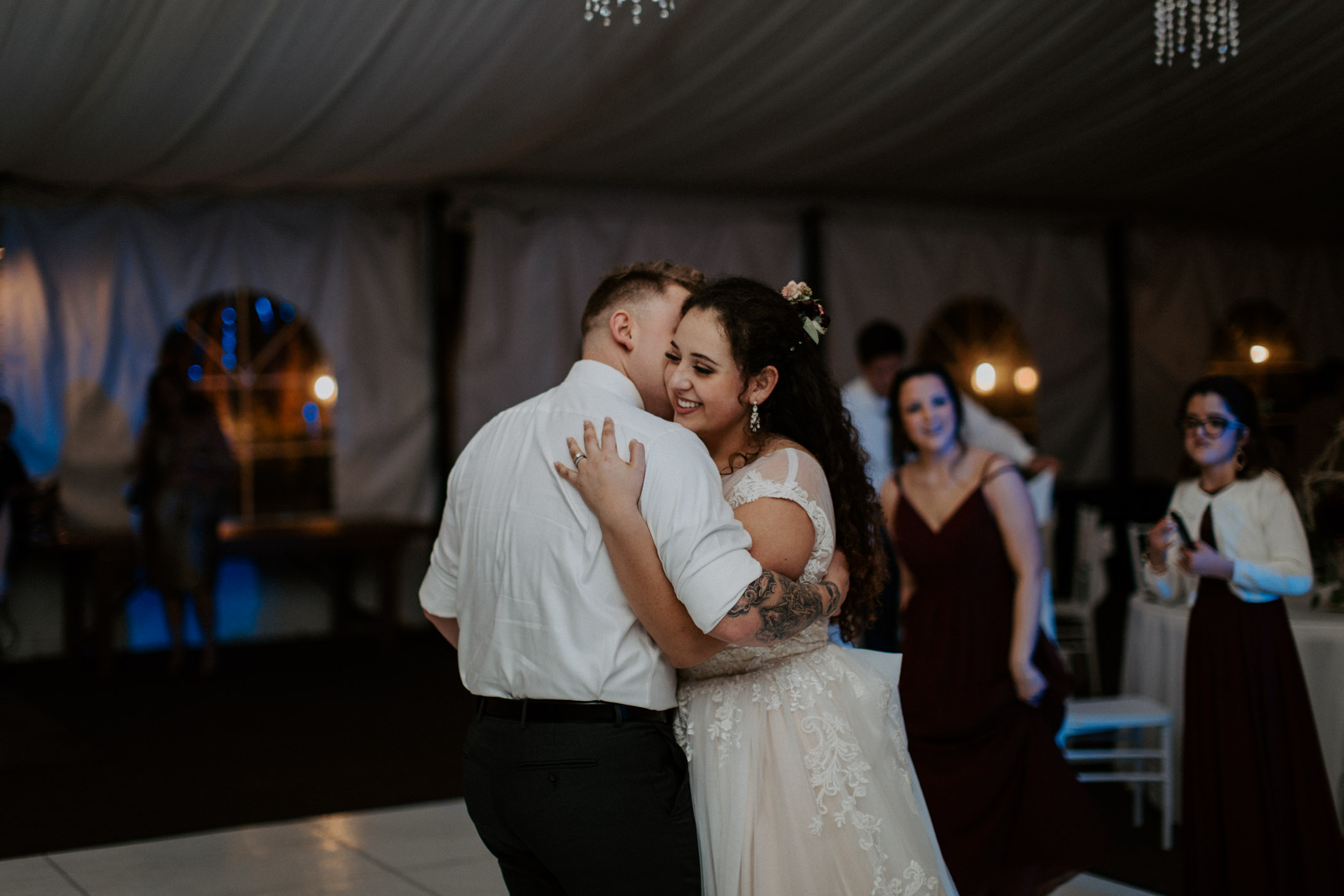 bride and groom golding each other and dancing at the end of their wedding day in California