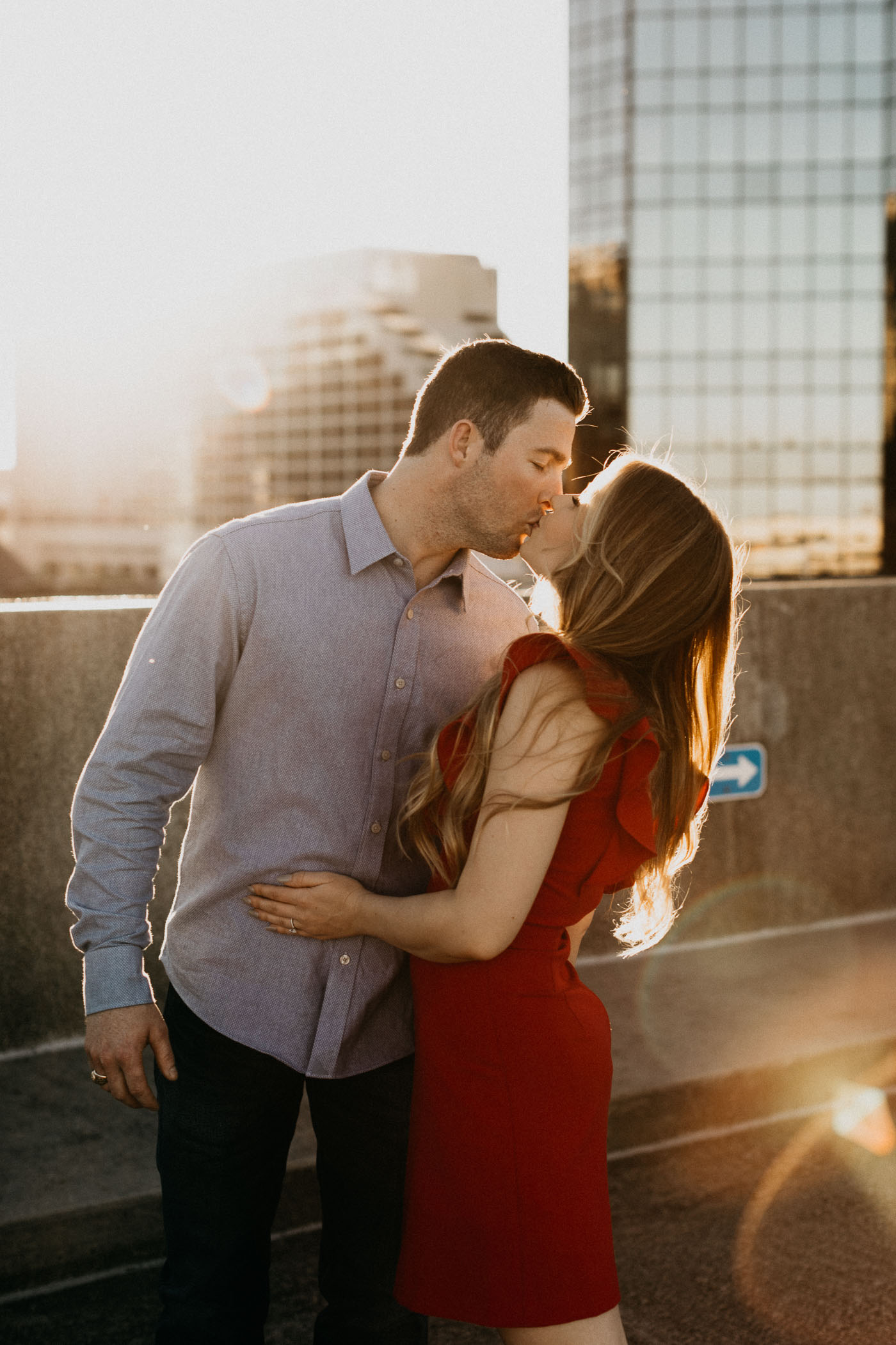 Engaged couple wearing red and blue taking photos on a rooftop at sunset