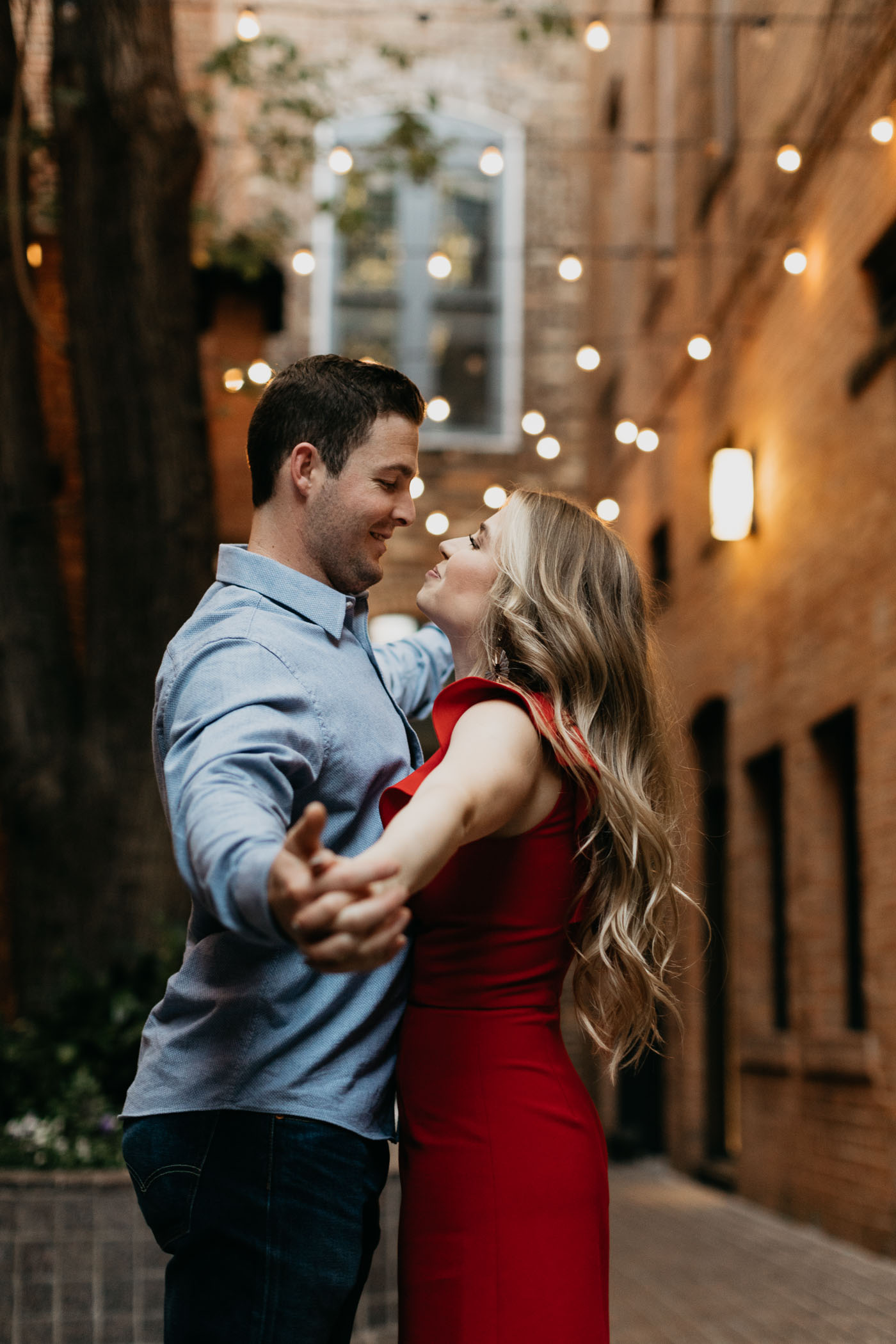 couple looking at each other romantically during engagement session in downtown fort worth courtyard