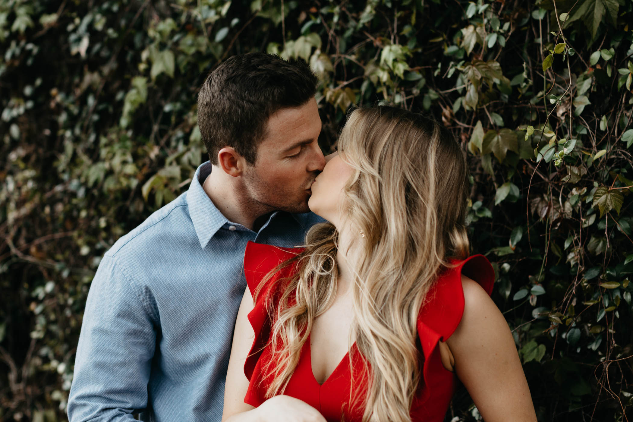Girl in red dress kissing fiancé in front of vine wall