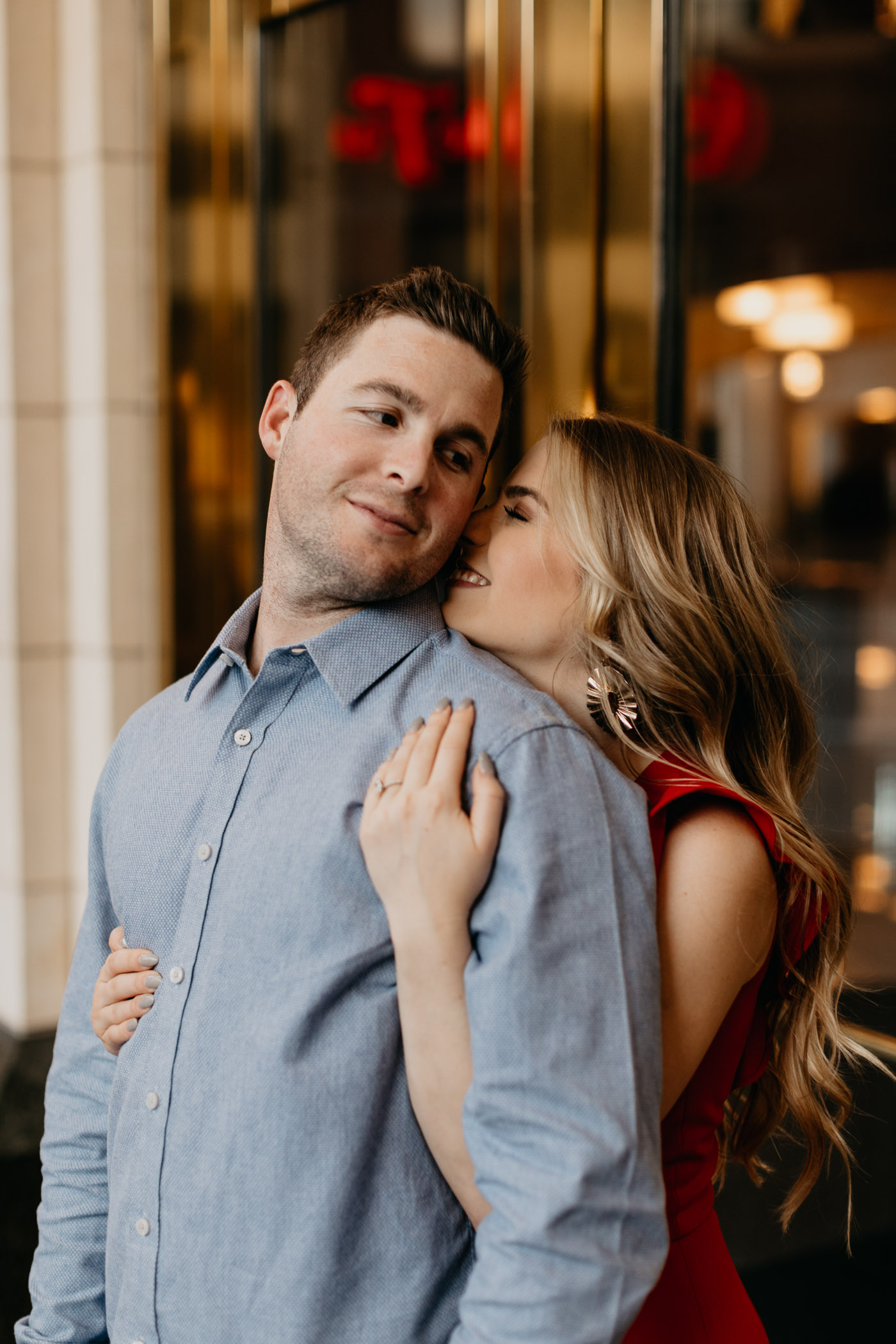 couple snuggling downtown during Fort Worth engagement session with Marissa Merrill Photography