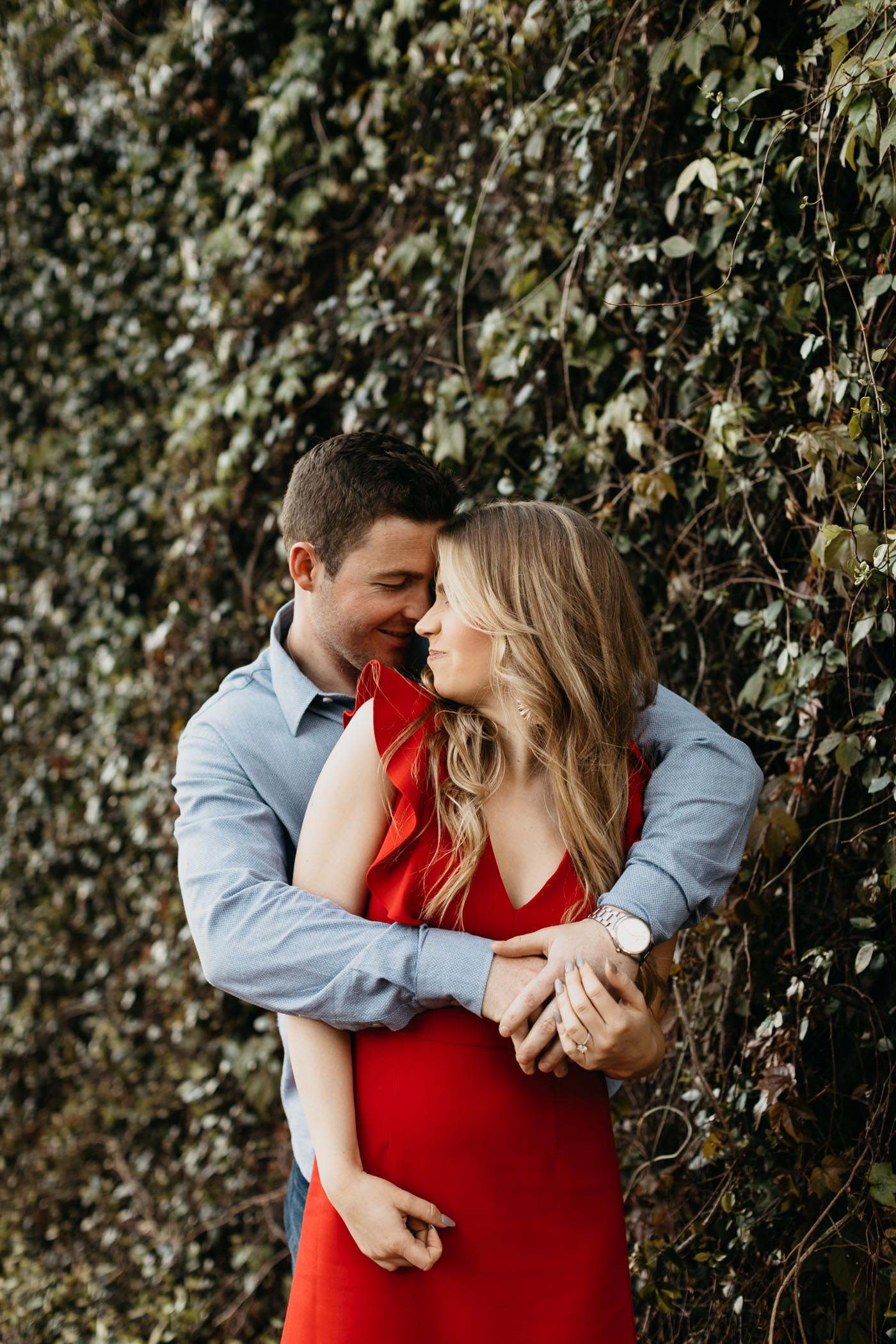 engaged couple wearing red and blue outfits taking photos in front of vine wall