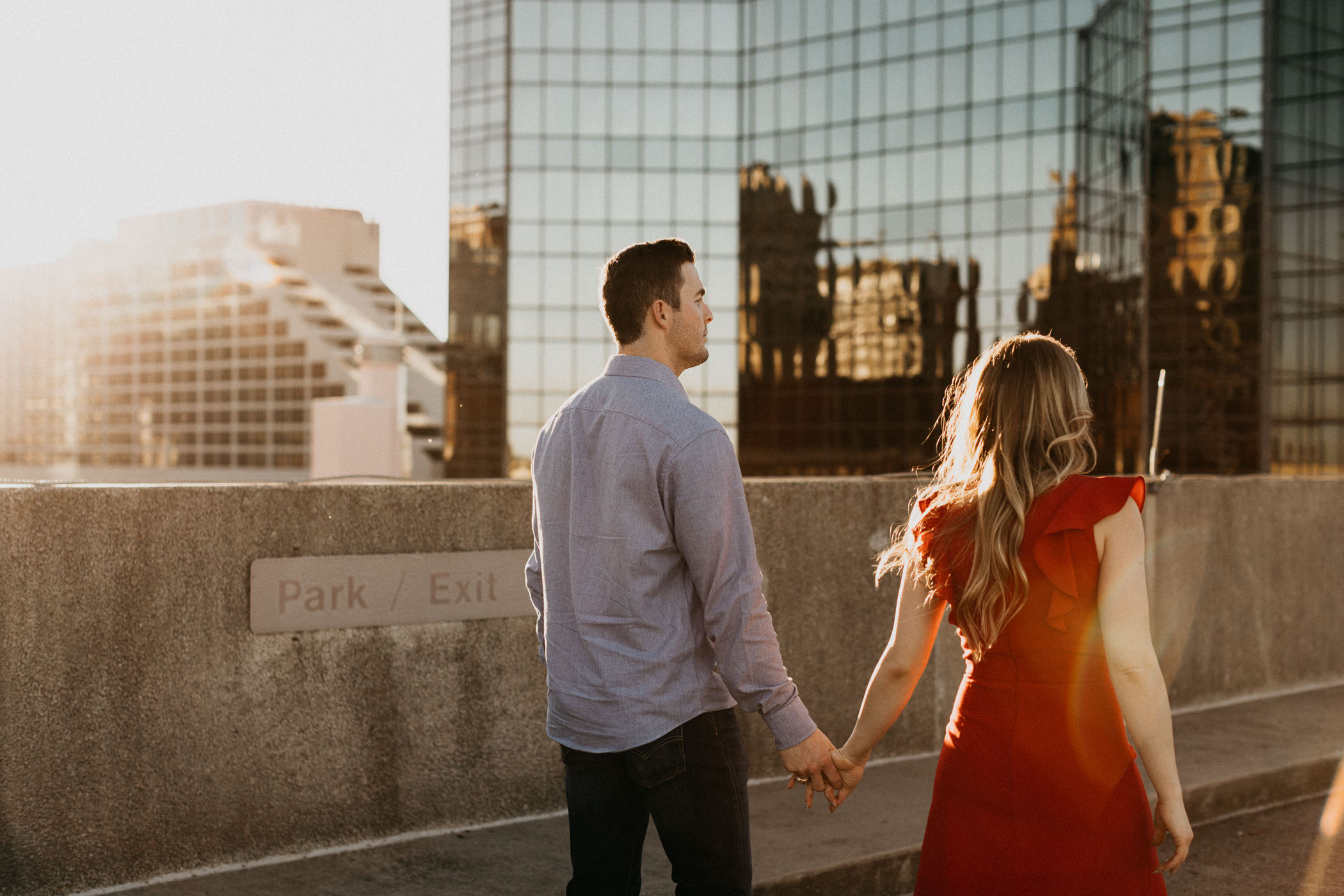 Couple walking on parking garage in downtown fort worth during engagement session