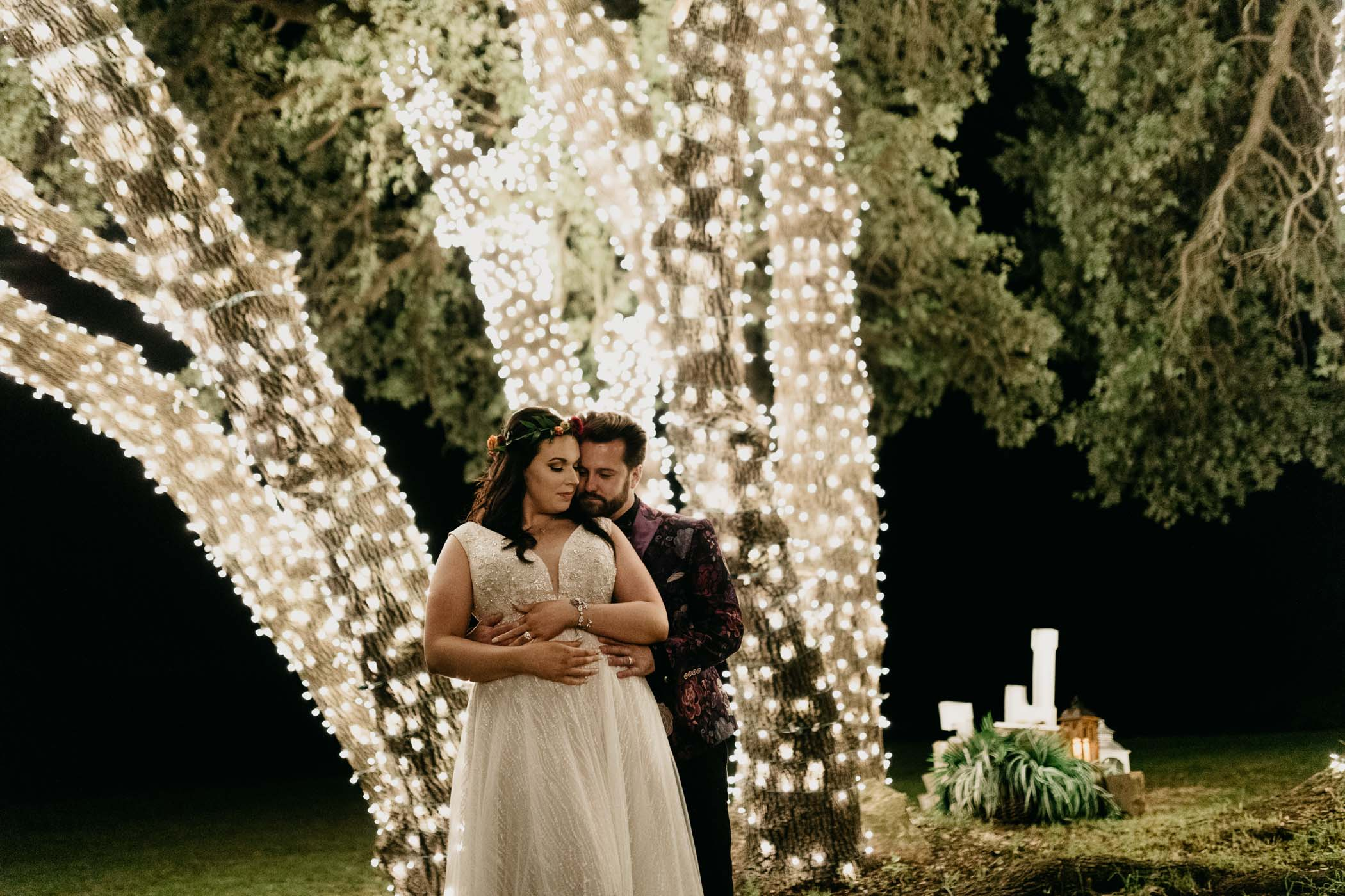 Tree wrapped in string lights used as backdrop for bride and groom portraits