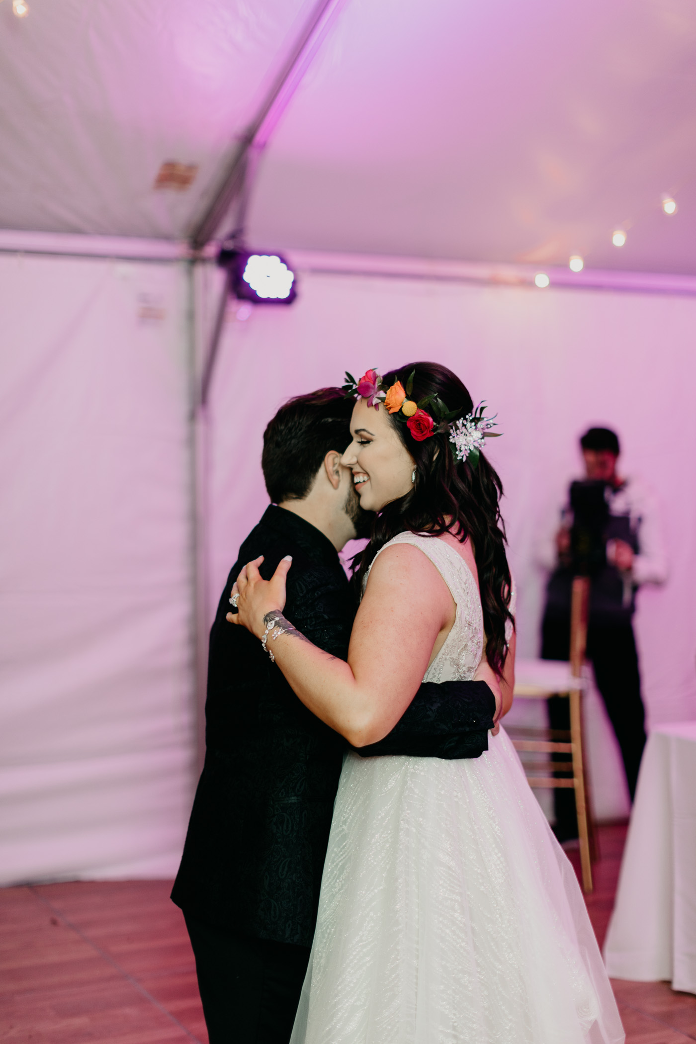 Outdoor wedding reception inside tent with purple lighting