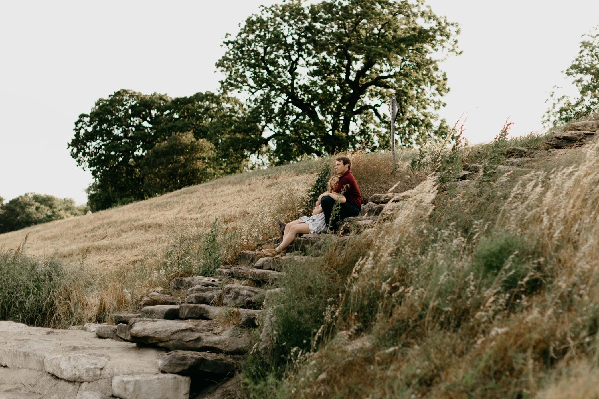 couple sitting on rock ledge during their engagement session at the trinity river in Fort Worth