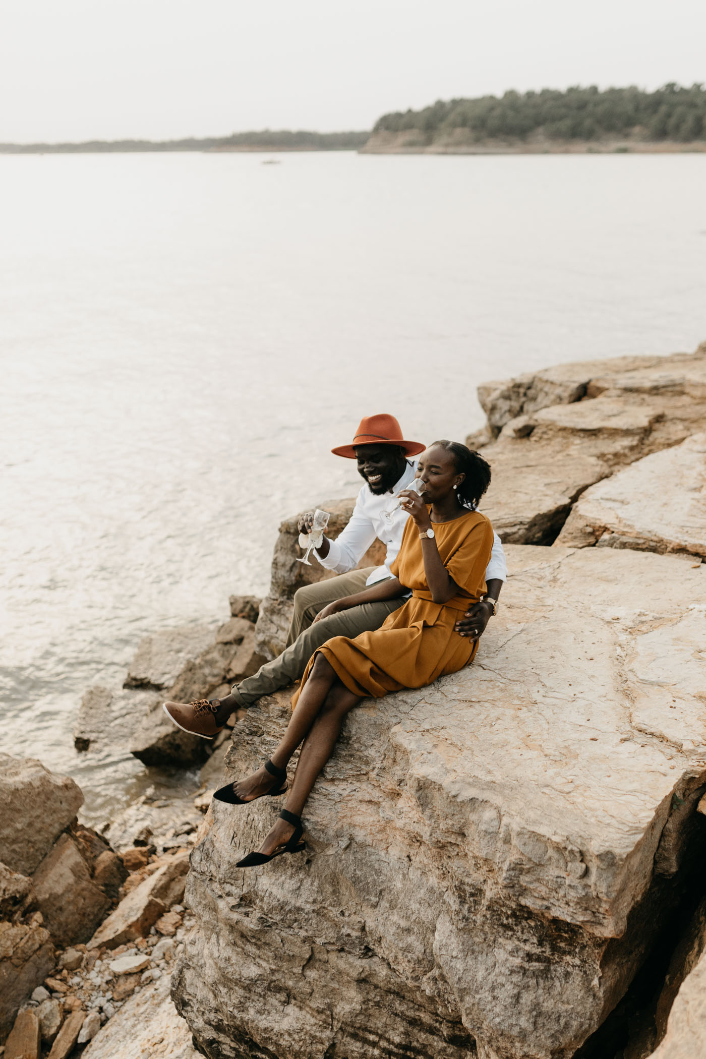 couple cuddling lakeside during anniversary couples photography session in DFW