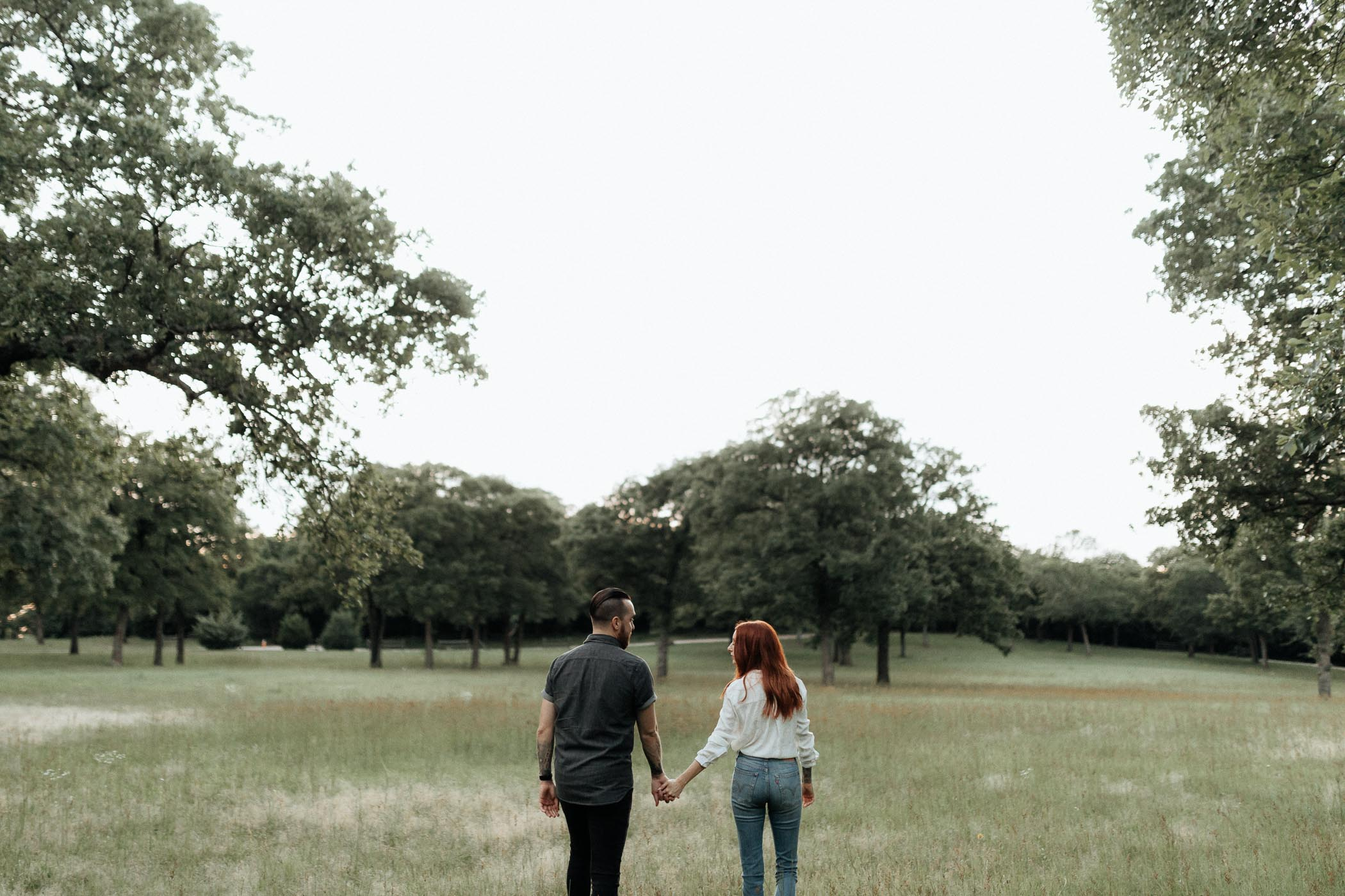 Couple walking in field at The grove in Aubrey texas at sunset
