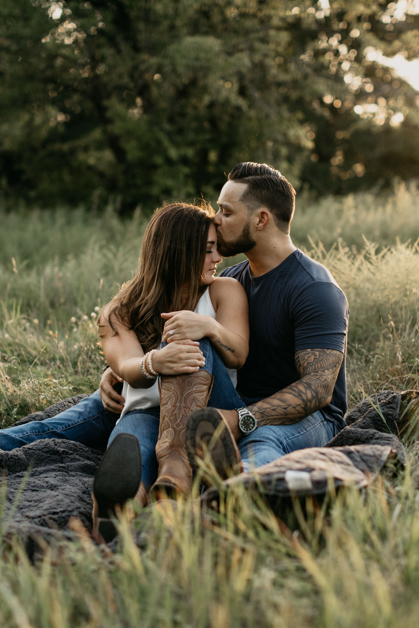 Couple sitting in grass being romantic