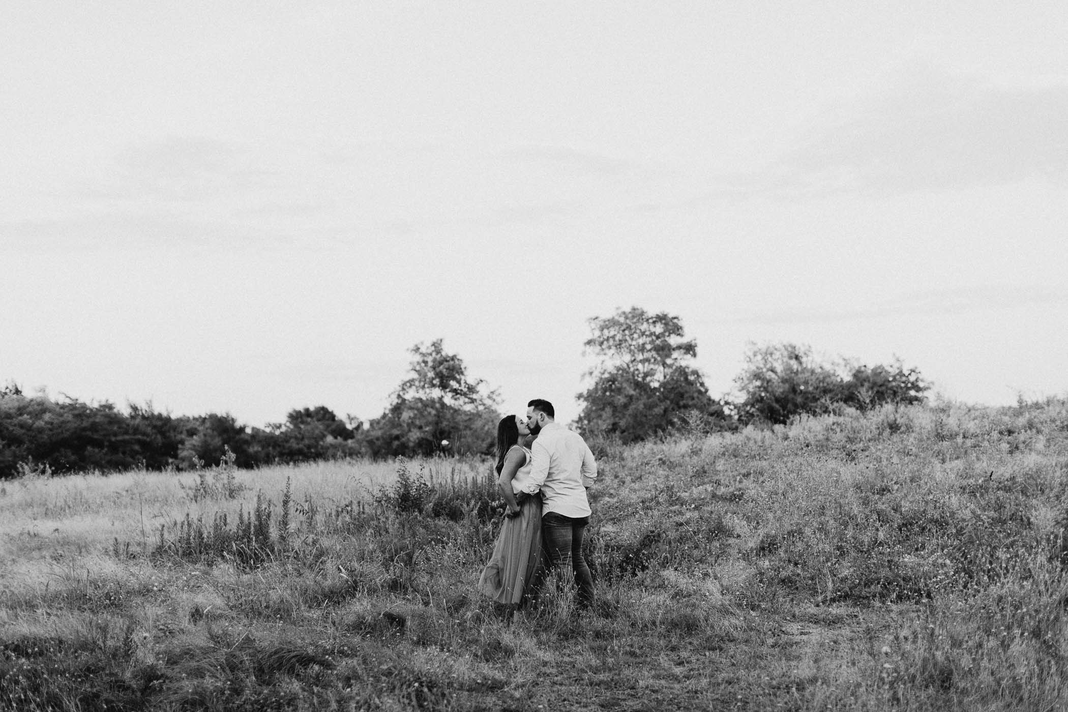 black and white of engaged couple kissing in field
