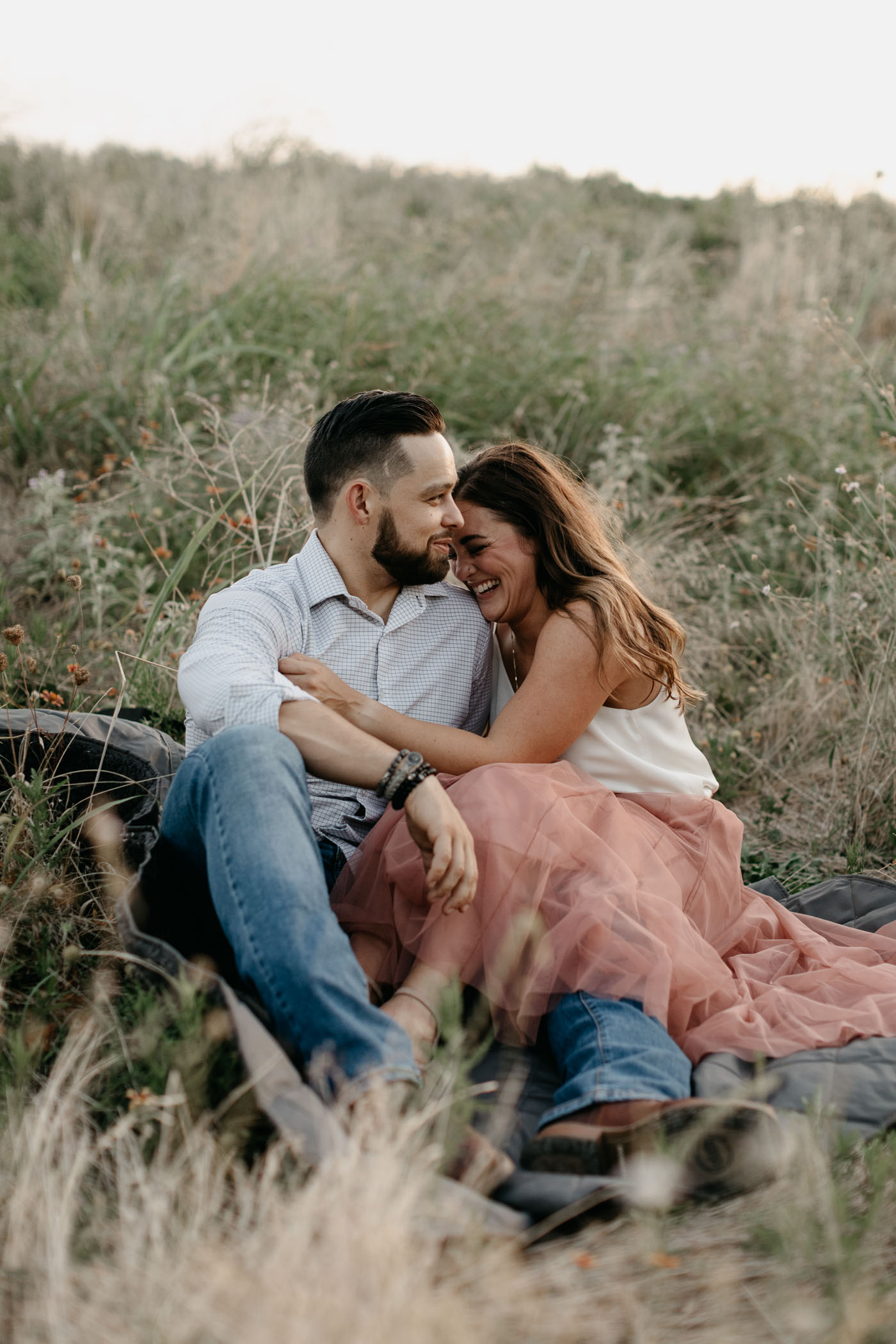 couple cuddling and laughing during engagement session in DFW