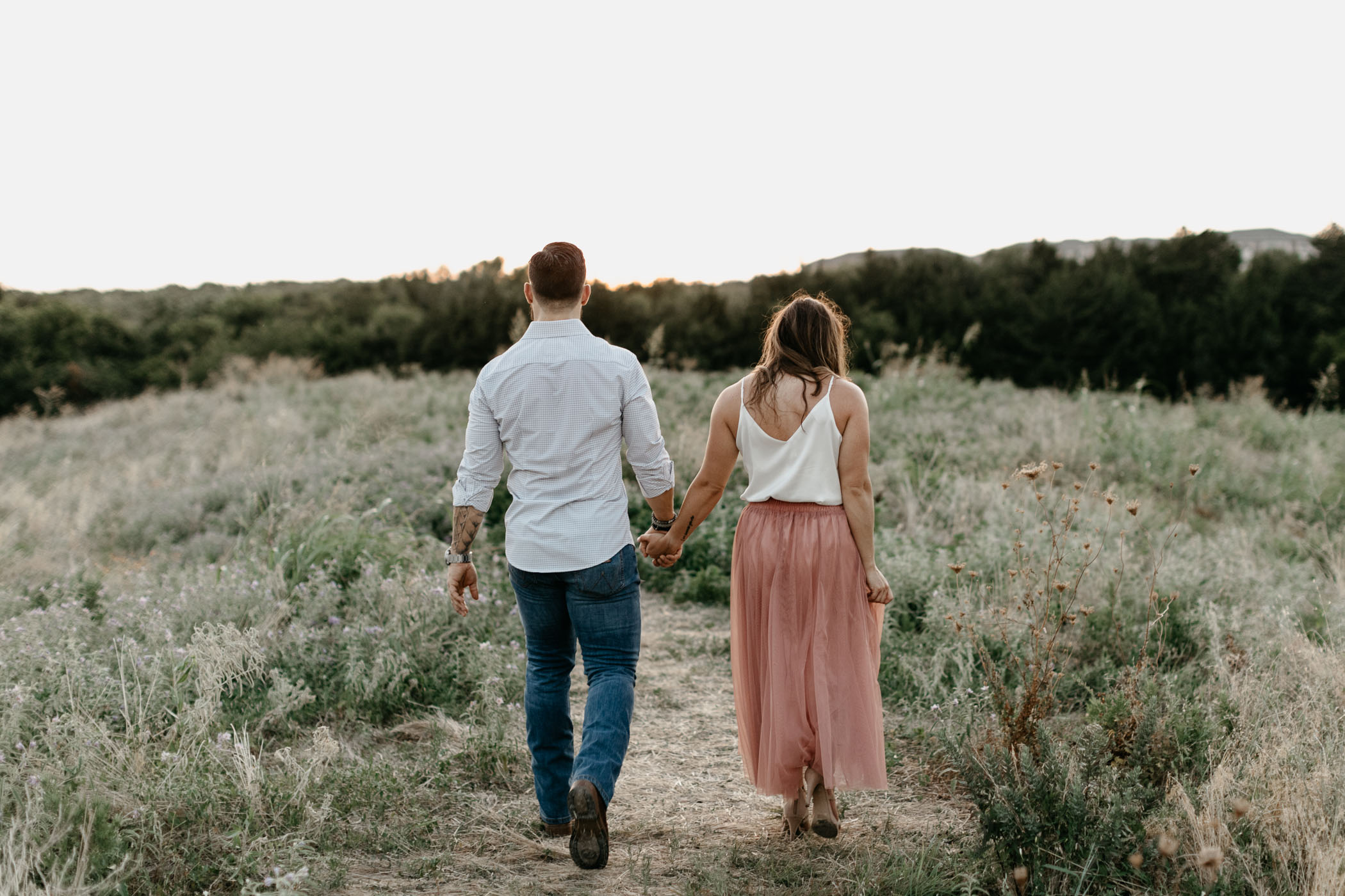 couple holding hands and walking away from camera in field