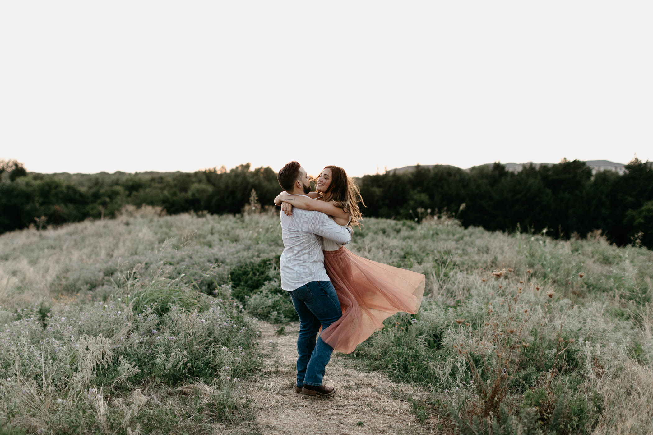 couple spinning around during engagement session in DFW