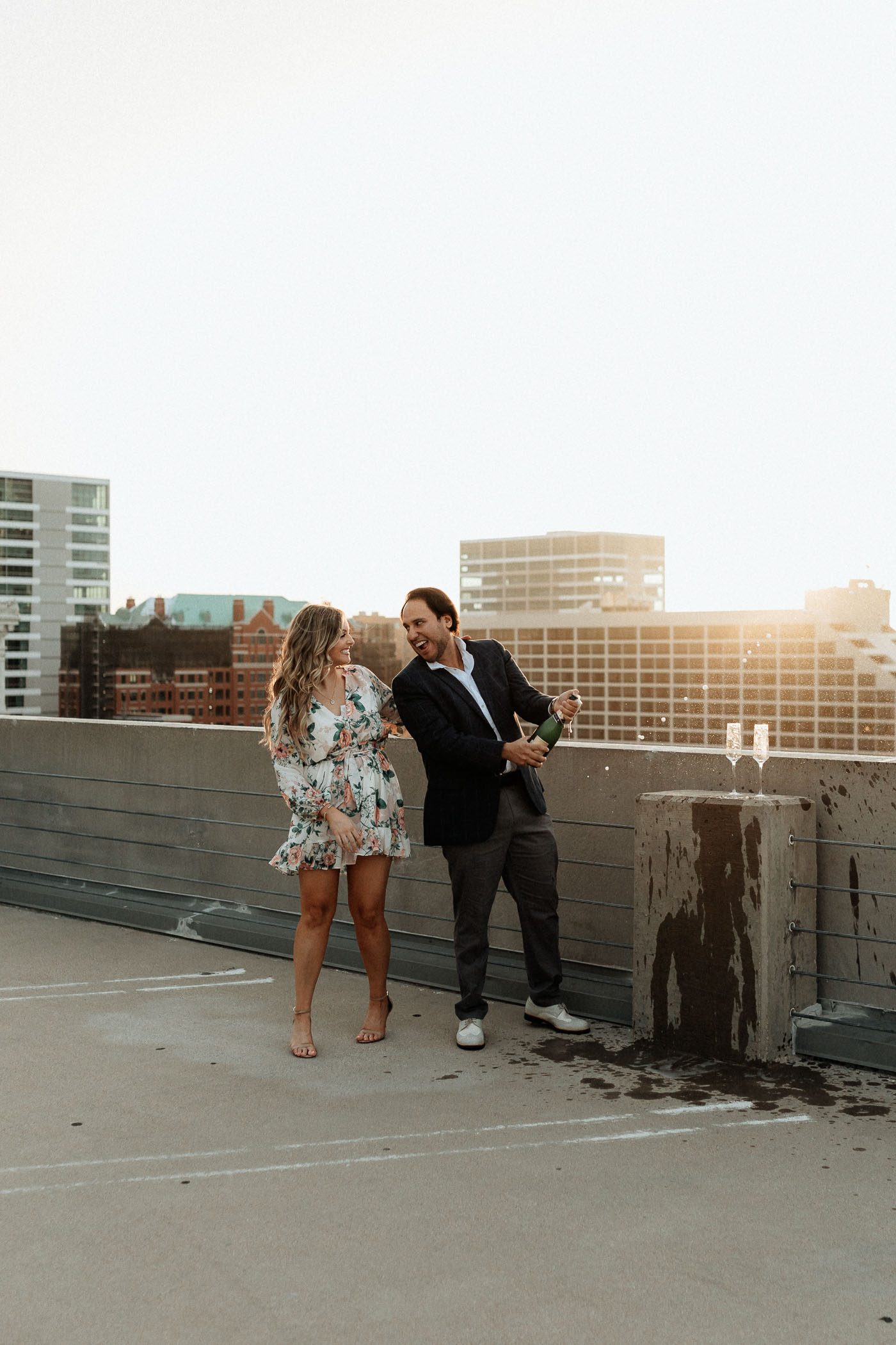 Couple popping a bottle of champagne on a rooftop at sunset for engagement photos