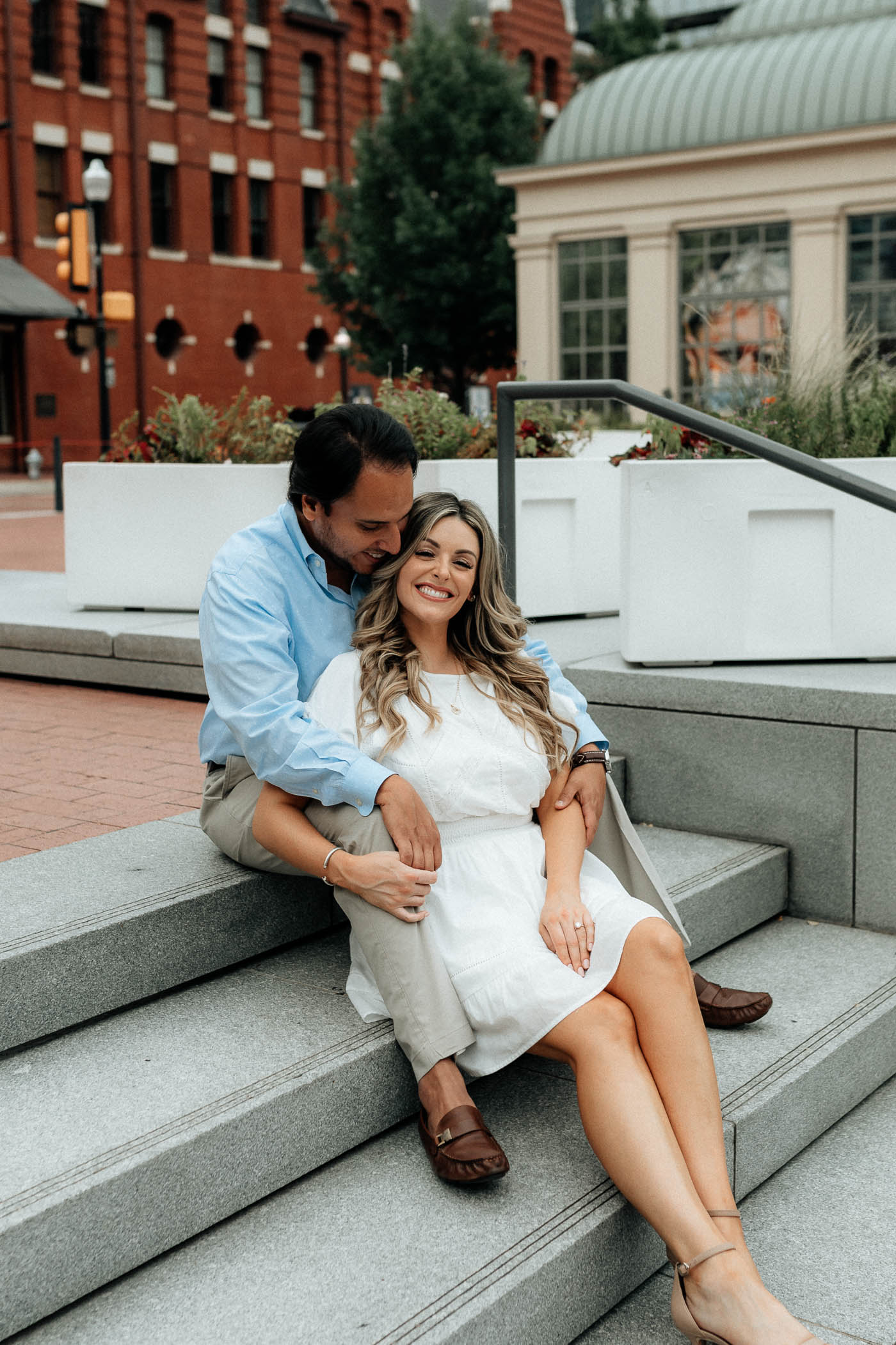 Couple sitting on steps downtown during engagement session in DFW