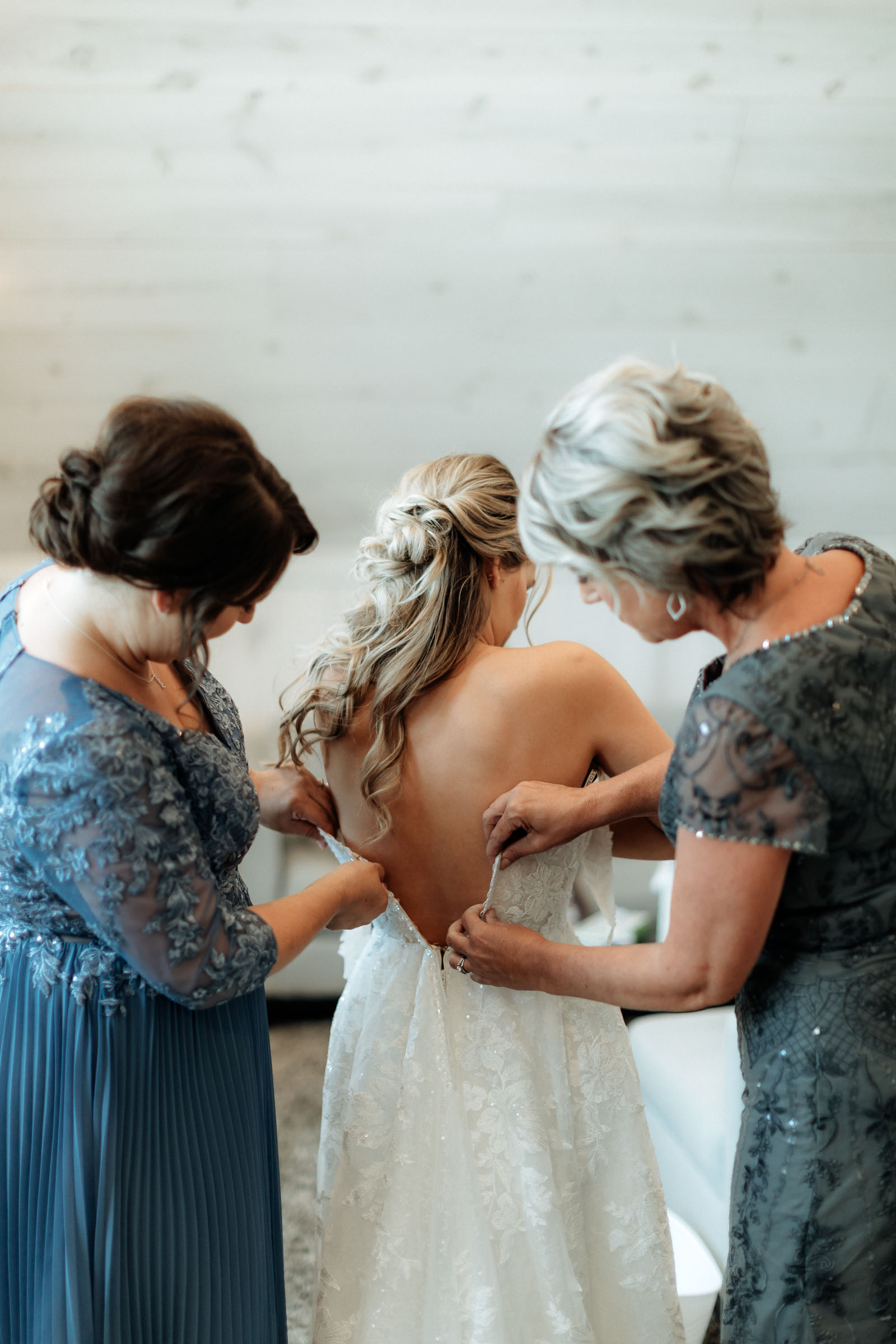 brides mom and mother in law helping her zip up her wedding dress