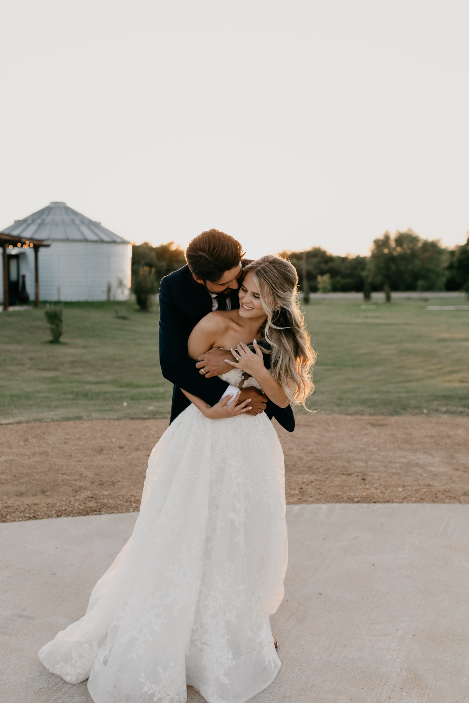 Groom hugging bride from behind at One Preston Events in DFW
