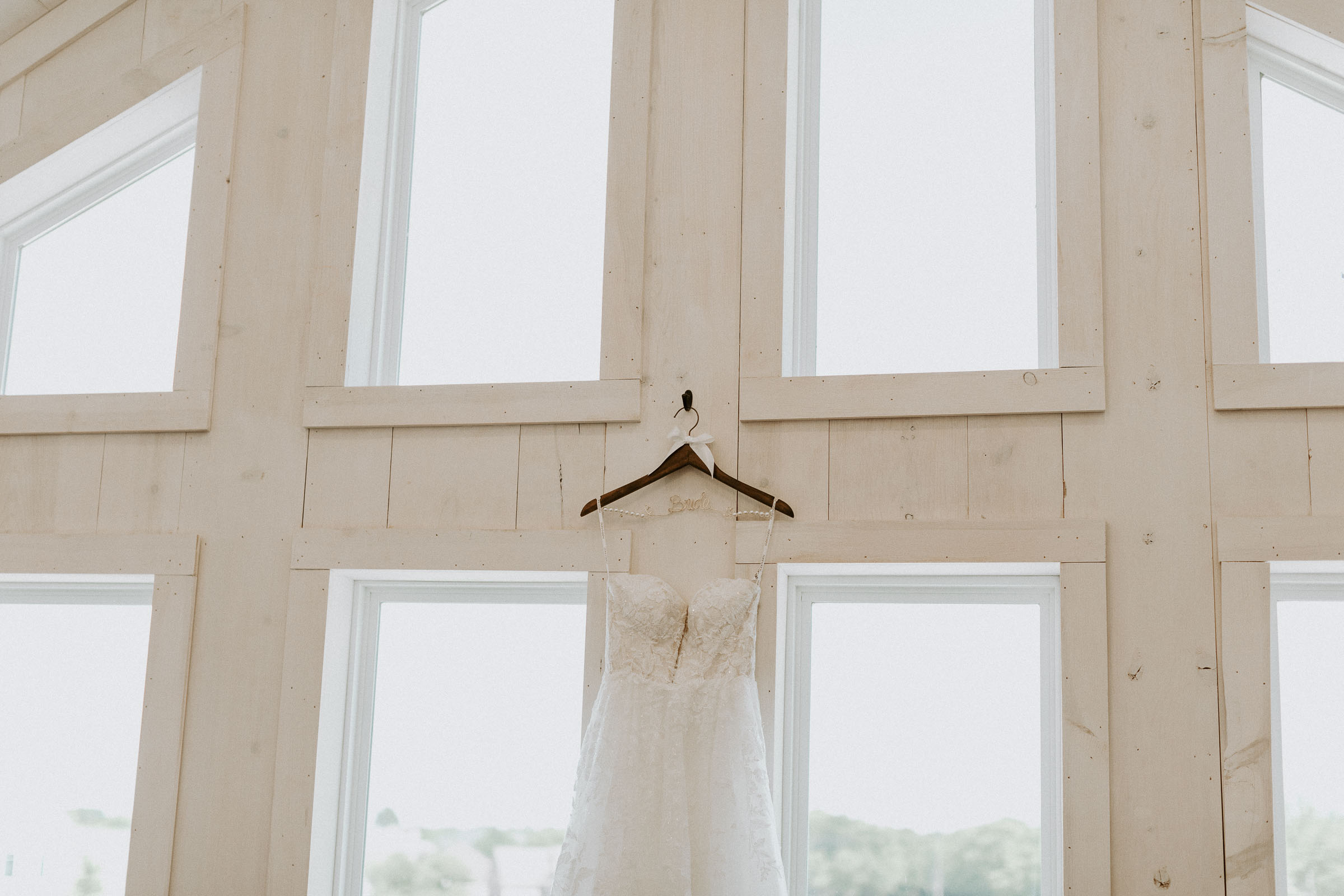 Beautiful wedding dress hangin by large windows on wedding day