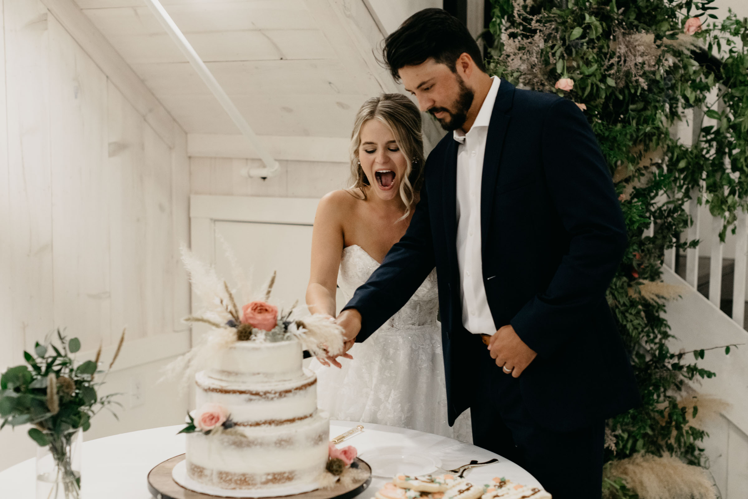 adorable couple cutting wedding cake during DFW wedding reception