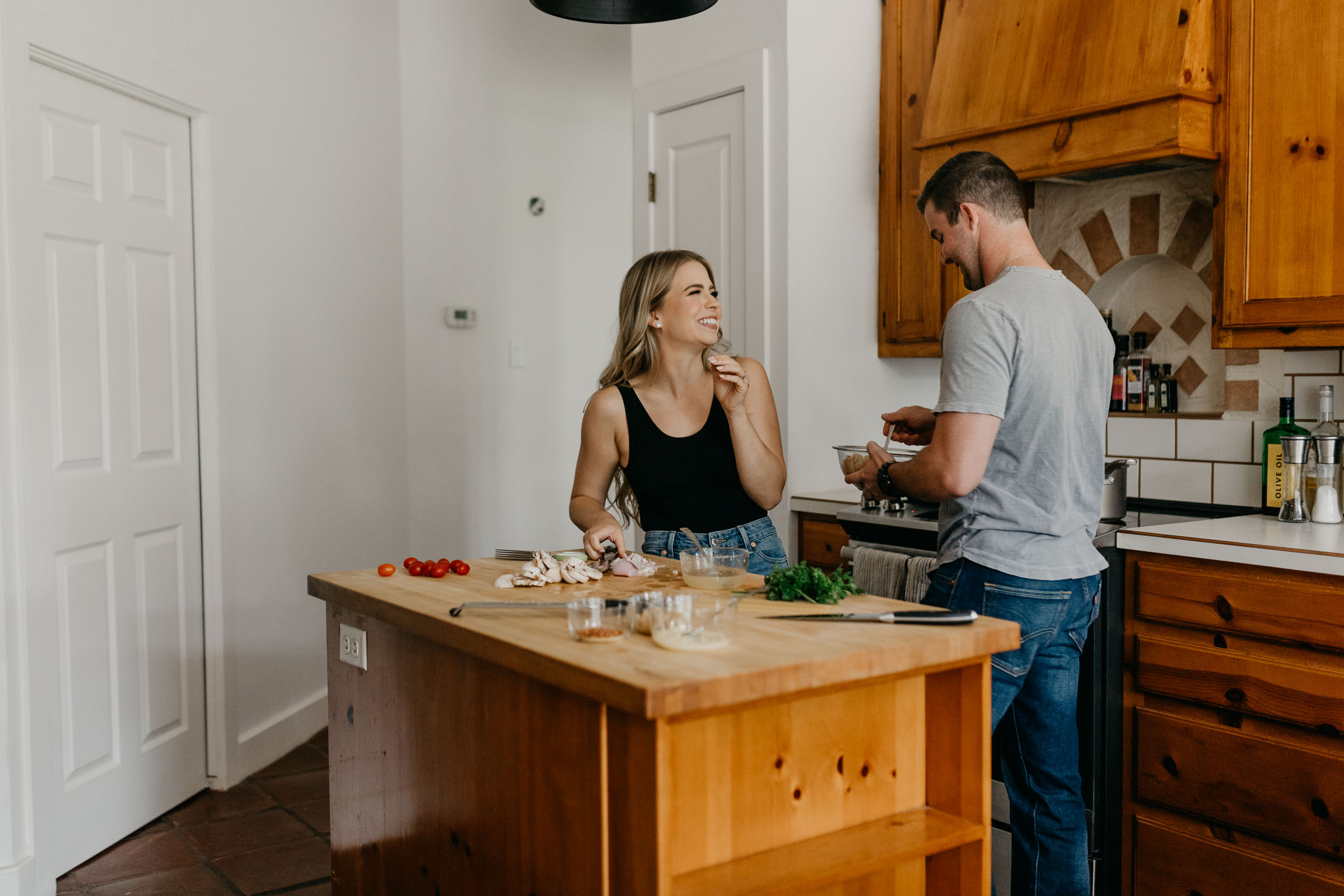 Engaged couple cooking dinner in their boho kitchen