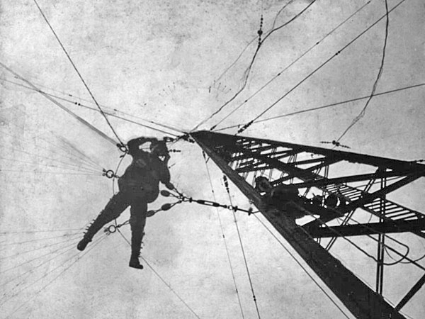 A rigger hangs from the 400 ft tall Awarua wireless station mast c1913