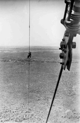 A rigger paints one of the upper guys, photographed from the attachment point for the lower guys