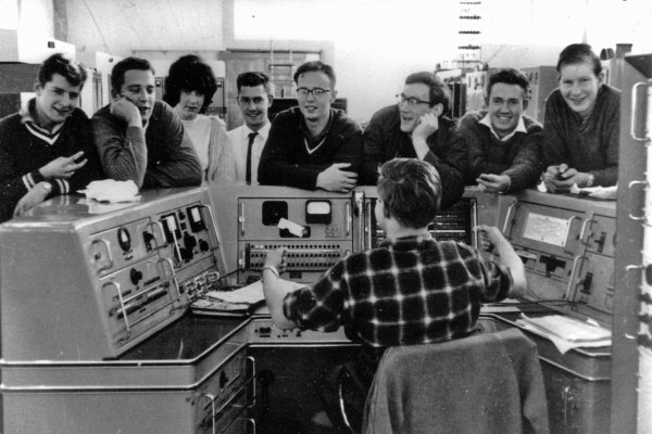 Himatangi Radio, probably late 1966. Noel McConachy at the control console, talks with L-R: Neil Crawford, Ian Wilton, Rose Peterson, Noel Beech, Leith Baker, Stan Hood, Chester Clark and Bruce Davenport