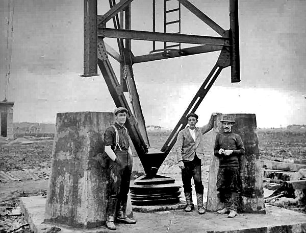 The completed tower standing on its pivot ball and glass insulators. L-R: Jas Twiss, Norm Furness, Eugene Reinhard (Telefunken Engineer)