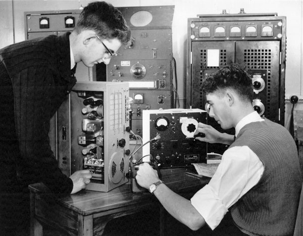 In this 1961 photo, trainees DC Moore (left) and AE Fletcher, both from Wellington, align a communications receiver using a signal generator and a multimeter. In the background is a 100 watt transmitter with its associated equipment, also used for training purposes.