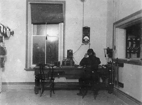 Operating room at Awanui Radio VLA, date unknown. The spark gap transmitter is see through the window at right, and part of a control panel can be seen at left.