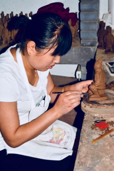 local Shaanxi artisan caving replicas of the famous Terracotta Warriors