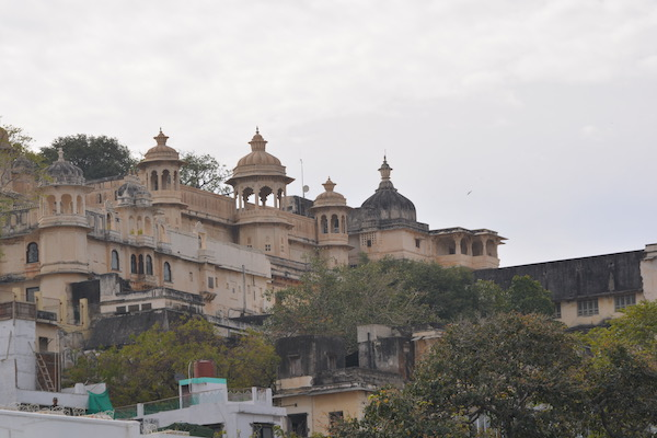 The city palace of Udaipur sitting at the top of a hill overlooking the city