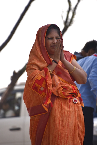 Indian woman wearing and orange sari praying at the Shri Om Banna shrine