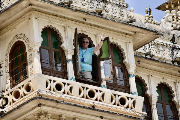 Man waving from an upper palace window at the Udaipur City Palace