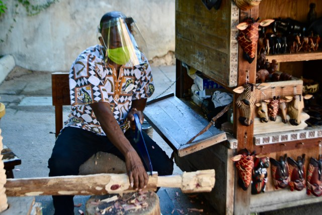 A Kenyan wood carver at Disney's Animal Kingdom wearing a face shield and mask during COVID 19