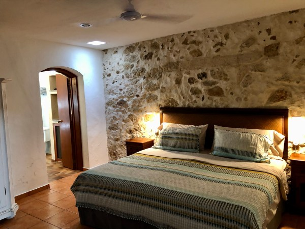 bedroom of our Merida Mexico airbnb with rustic wall and huge bathroom