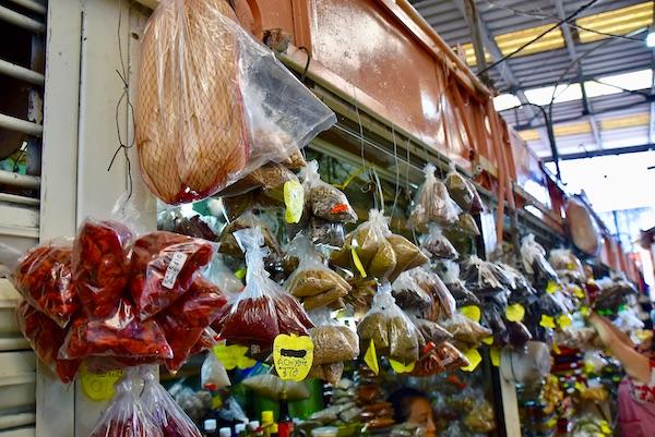 colorful bags of spices hanging in a spice market in the Lucas de Galvez Mercado in Centro Merida Mexico