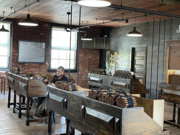 man hand rolling cigars at the El Reloj factory in Tampa Florida