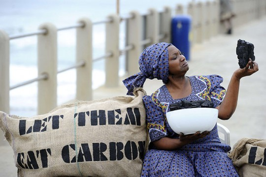 a dark skinned woman in bright blue modern African dress and matching headdress sits next to a large sack that says LET THEM EAT CARBON - she is holding a bowl of coal and holding a large piece up as if she is about to eat it