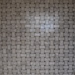 Small white marble tiles with grey veins in basketweave pattern