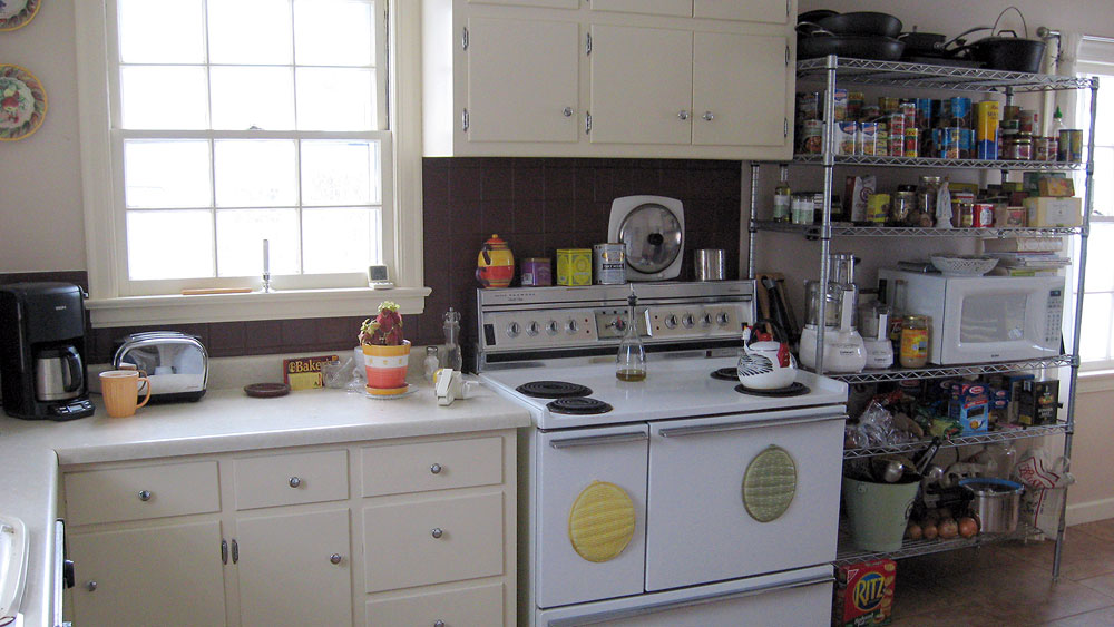 Home kitchen with Sears Kenmore oven range, pantry, kitchen cabinets