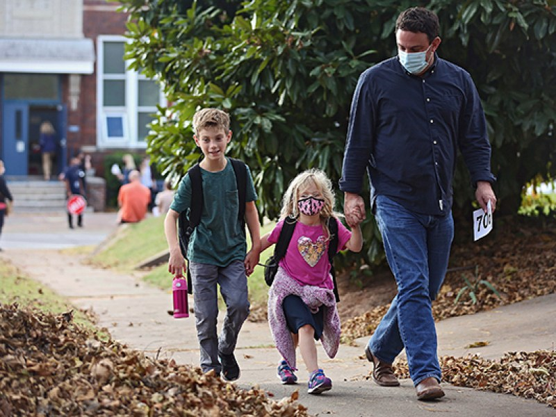 Wes Holmes, right, walks with is daughter Hollace Holmes after her first day of pre-kindergarten at Council Oak Elementary School in Tulsa, Okla., Monday, Nov. 9, 2020. Tulsa Public School returned to in-person instruction for kindergartners and pre-kindergartners on Monday, amid the coronavirus pandemic. At left is Dawson Holmes, 8, his son and Hollace's brother. (Mike Simons/Tulsa World via AP)