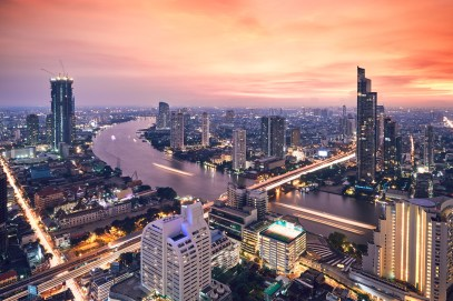 Bangkok during golden sunset. City skyline with traffic on the roads and Chao Phraya River.