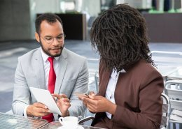 African American businessman and woman looking at digital tablet