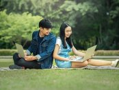 two young people using laptops outdoors