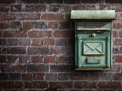 a green mailbox attached to a wall