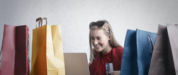 Woman with multiple shopping bags is on a laptop