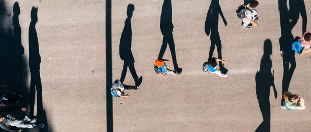 People walking alongside their shadows.